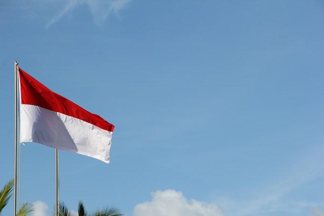 bendera Indonesia tengah berkibar di lapangan