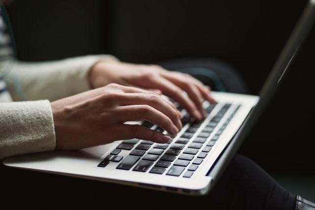 seseorang memperagakan cara menulis esai menggunakan laptop