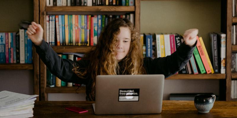 seorang anak perempuan sedang belajar bahasa inggris online menggunakan satu laptop